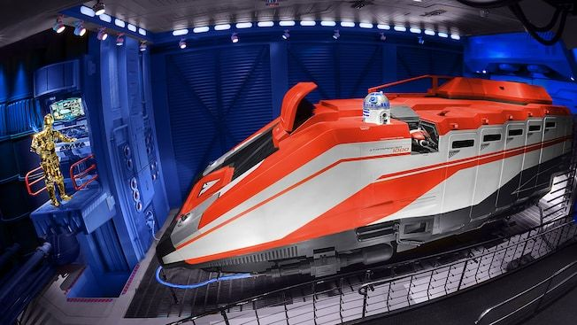 R2-D2 sits atop a Starspeeder 1000 vehicle near the queue at Star Tours - The Adventures Continue