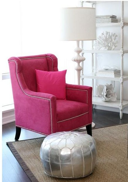 Pink chair with silver nail head trim, the white lamp  book shelf and the awesome silver pouf