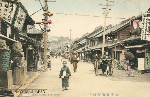 1900's. Noge, Yokohama. A small boy looking straight into the photographer's lens, a man pulling a cart, a shopkeeper sticking his head out of his shop to look down a street full of shops. This simple scene, immortalized by an anonymous photographer on a day in the early 1900s, shows a street that once was Yokohama's main route of entry, Nogemachi-dori.