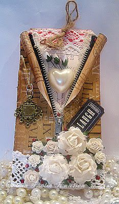 handmade zipper tage ... collage look with artificial flowers, a medal, edge die, pearls ... shaped like a ladie's jacket ... great tag!!