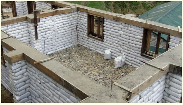 Sand earth bag building with rammed earth around top...