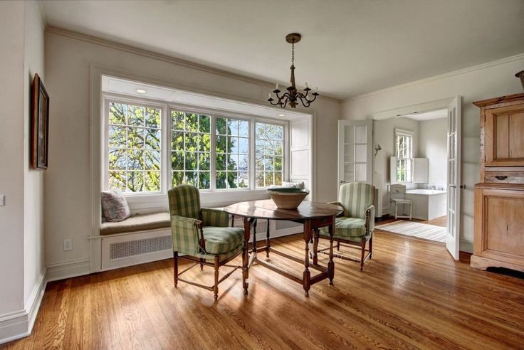 Traditional Dining Room with Bay window, Crown molding, Chandelier, Custom Bench Cushion - Standard, French doors