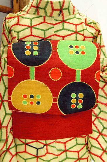 赤に水玉が6つ並んだボタンのような大きな円のモチーフが染め出された紬の名古屋帯です。