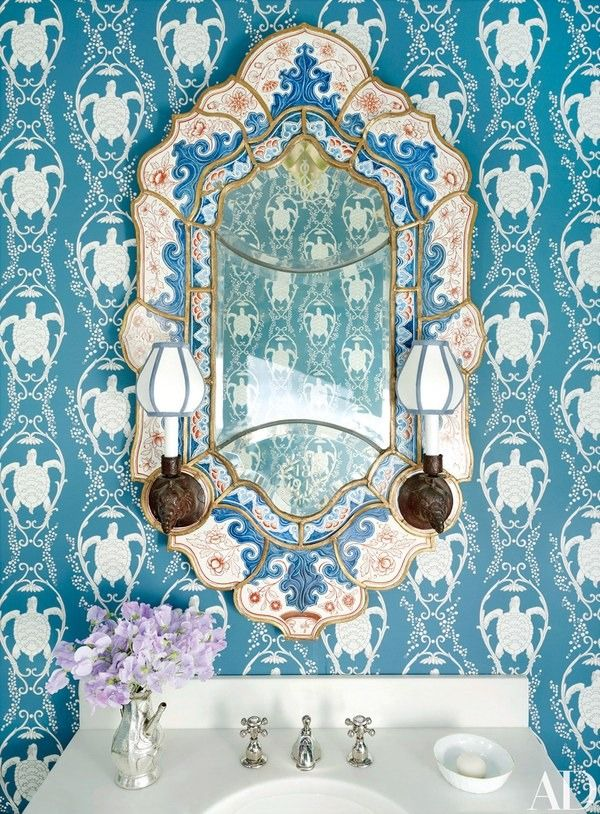 In architect Peter Pennoyer and designer Katie Ridder's New York home, a wall covering by Ridder and an antique mirror retrofitted with elephant sconces lend pizzazz to a powder room | archdigest.com