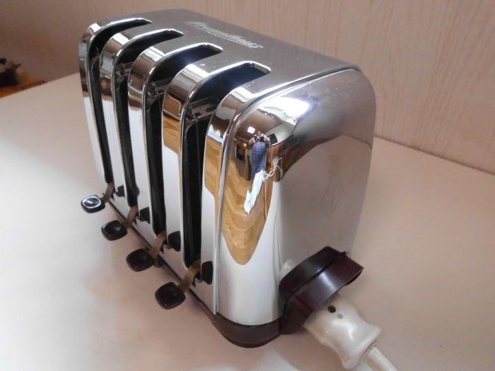 Aan het begin van de jaren 1950 brengt PROMETHEUS  deze broodrooster, op de markt,  een model voor horeca -inrichtingen of grote keukens. Zijn voordeel? Met behulp van vier units en individuele push-buttons kunnen tot vier sneetjes toast individueel worden gegrild!  De functionele en stoere toaster imponeert met een gepolijst roestvrij stalen behuizing in combinatie met donker rood bakeliet  (h: 20 b: 28 d: 17 cm). Elke  sleuf heeft een aparte hendel.. Een operationele groen licht brandt…