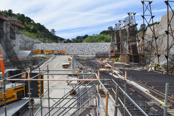 Contractors for the U.S. Army Corps of Engineers Sacramento District continue work on the lower chute of the Folsom Dam auxiliary spillway project April 1, 2015 in Folsom, California. Concrete walls are being installed along the sides of the lower chute to contain water released from the new spillway as it flows along a 200-foot drop to the stilling basin and enters the American River. The U.S. Army Corps of Engineers Sacramento District, together with the U.S. Bureau of Reclamation and…