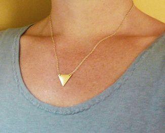 Collier Triangle. Collier géométrique orné d un pendentif triangle monté sur une chaîne en métal doré. Le pendentif triangle mesure 1.8cm.