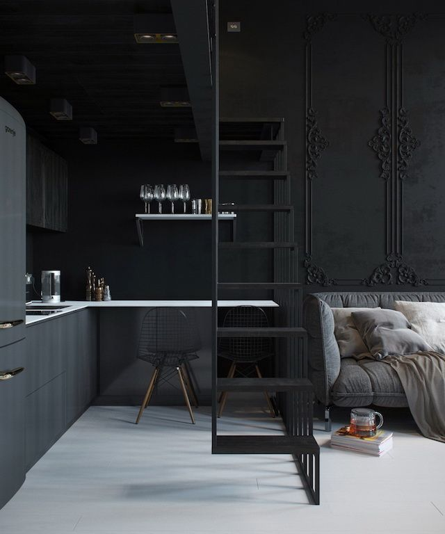 elegantly dark open kitchen : black, white accent, wall panelling boiserie, grey sofa. {^ French By Design}