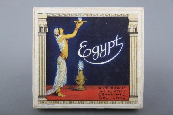 Forssan museo. J&E Humelin tupakkatehtaan savukeaski, jossa ollut 25 valmiiksi käärittyä savuketta. Savukkeet ovat Egypt-merkkisiä. Rasia on suorakaiteen mallinen. Kansi on koristeltu Egypti-teemaisesti ja siinä on harsoihin pukeutuneen naisen kuva. Nainen kannattelee tarjotinta korkealla ilmassa. J&E Humelin oli Turkulainen tupakkatehdas, joka perustettiin vuonna 1881. Pakkauksen on valmistanut Turun Kirjapaino Oy.