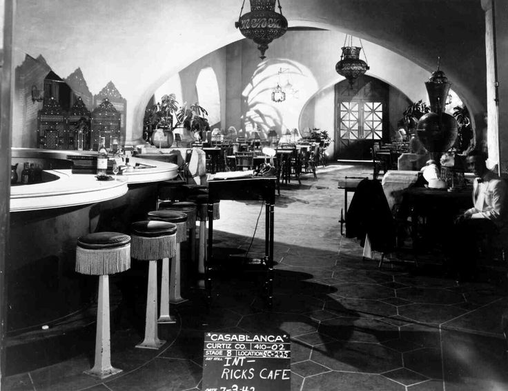 Set shot of Rick's Cafe; Humphrey Bogart as Rick Blaine sitting in shadows on right.