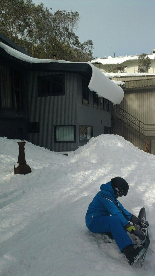 Snow curve falling from lodge roof