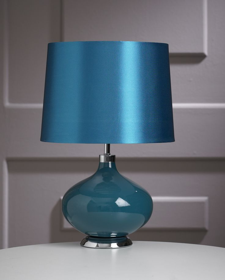 The Juno is a distinctively elegant table lamp; it features a bowl shaped base with a chrome style bottom, cap and stem, and comes with a matching shade.