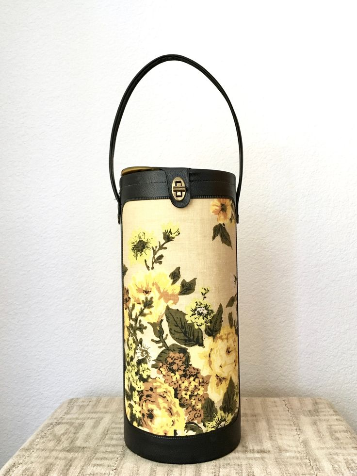 Super cool vintage knitting case with a carrying handle and lots of room for your knitting projects!This could also be easily repurposed to carry maps or large documents, or many other items. It has a beautiful floral pattern on both sides with yellow roses and other flowers and foliage, with black vinyl trim and a brass toggle clasp for the lid. It has a metal base that is covered by black vinyl on the outside.There is a small cutout on the lid to slide your needles i...