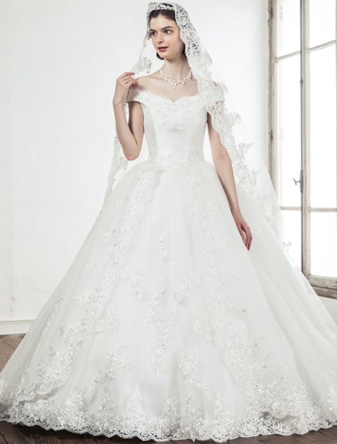 オフショルダーの身頃にビッグラインのロングトレーンのスカートがゴージャス感漂う、オーセンティックなマリエ。 ライティングで浮き立つシルバーコードレースの輝きが印象的な格調高い装い。ペアのマリアベールがより一層花嫁を引き立たせる。