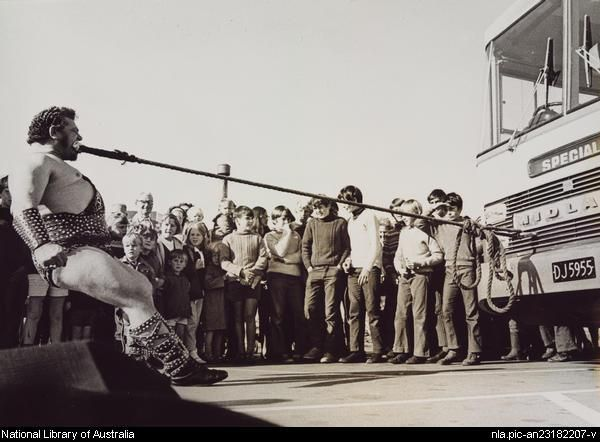 Portrait of Simon Spiteri pulling a bus with a rope held in his mouth, ca. 1960. Collection: National Library of Australia