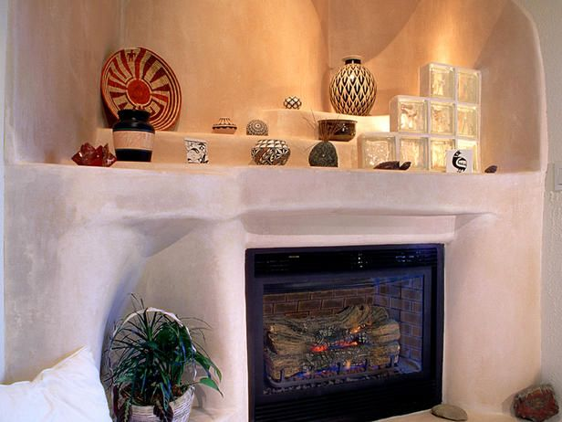 An organic sculptural form provides the surround for this fireplace and intrinsically creates shelves for displaying a lively collection of pottery.