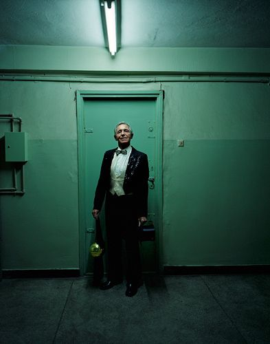 Zdzislaw Niemeczek (63) posing for portrait in illusionist dress at the corridor of the housing block he lives. For 46 years, he had been performing as an acrobat and illusionist artist. He has been retired for 8 years. He started to perform as a 10 years old boy