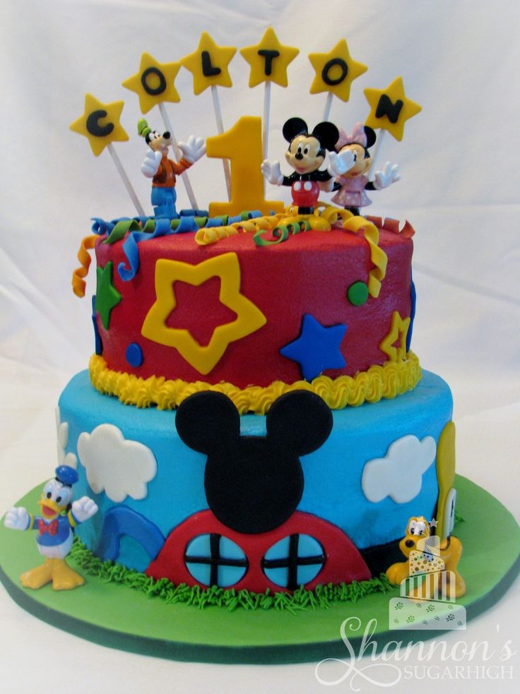 Mickey Mouse Clubhouse Cake. 2-tiered cake that is iced in buttercream with fondant accents. Bottom layer is vanilla and top layer is chocolate. Lots of bright colours including blue, red, green, and yellow; perfect for a child's birthday party.