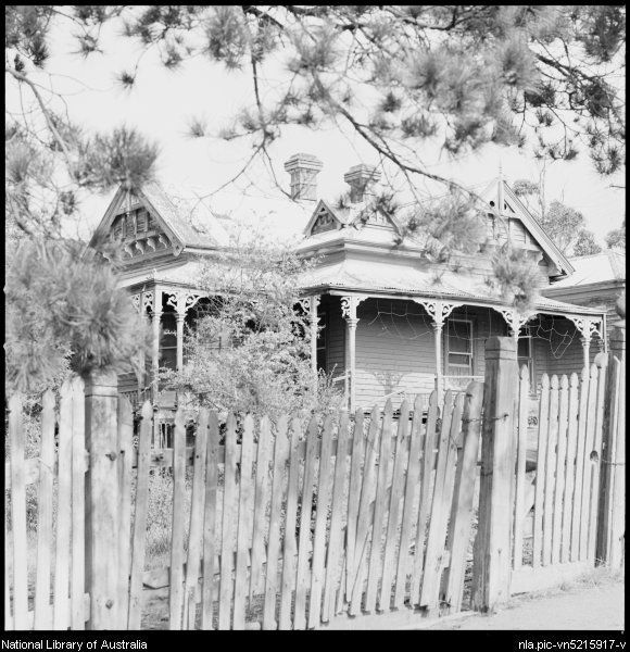 Stacey, Wes (Wesley), 1941- Weatherboard Victorian style residence viewed over a fence, Maldon, Victoria, ca. 1970 [picture]