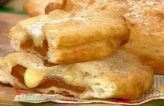 Hacer la masa de torta fritas y dejar descansar. Estirar la masa y cortar discos. Colocar cubitos de dulce de membrillo y queso sobre un disco, tapar con otro, pegar bien y freír en aceite caliente. Pasar por azúcar.