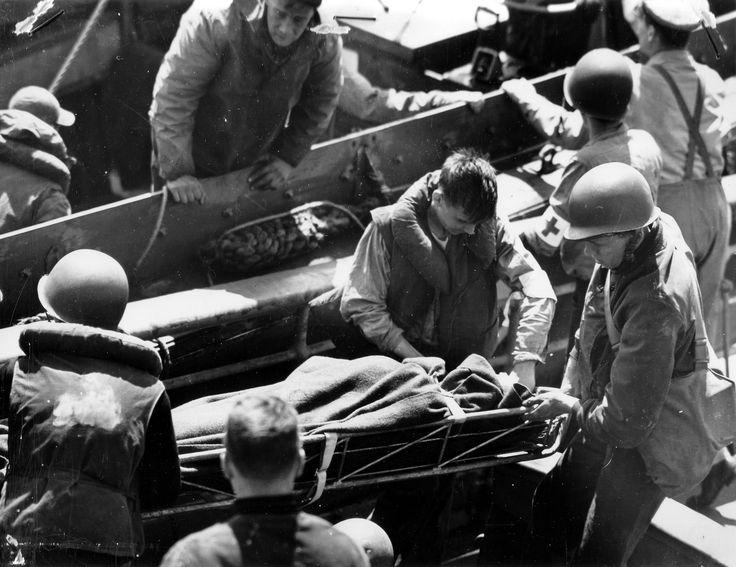 https://flic.kr/p/ejvf73 | p012553 | Transfert d'un blessé allongé sur un brancard et  recouvert  de couvertures, d'une barge vers un navire de plus grande taille. Deux medics avec brassard  Croix-Rouge Le photographe est sur l'USS Samuel Chase APA-26, sous réserve toutes ces photos sont de : Robert F. Sargent, voir ici : en.wikipedia.org/wiki/Robert_F._Sargent La p012546 a été prise du même endroit mais avant, au départ des troupes à débarquer : www.flickr.com/search/?w=58897785@N00&q=p0125