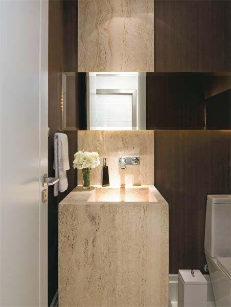Bancada em mármore travertino bruto e espelho na horizontal com iluminação embutida são o diferencial neste lavabo