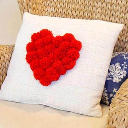 Pillow with red pom-pom heart