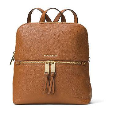 "Rhea medium slim leather backpack by MICHAEL Michael Kors. MICHAEL Michael Kors pebbled leather backpack. Golden hardware. Flat top handle, 2. 5"" drop. Adjustable shoulder stra..."