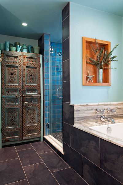 The highlight of this bathroom are the two antique Moroccan doors that were affixed to a new custom cabinet. The backsplash consists of gray tile that extends to the back wall and contrasts well with the brighter accent hues of the Moroccan doors.: Bathroom Design, Edha Bathroom, Dark Bathroom Brighter, Bathroom Oth, Bathroom Downstairs, Moroccan Bathroom, Bathroom Ideas, Blue Colors, Bathroom Tile