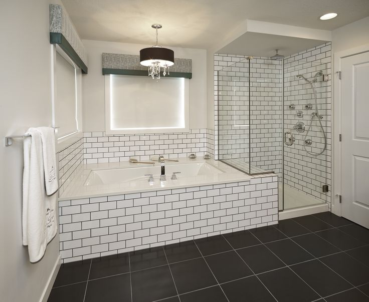 Crisp white subway tile accented with dark grout surrounds the tub and enclosed shower at the for White subway tile with black grout bathroom