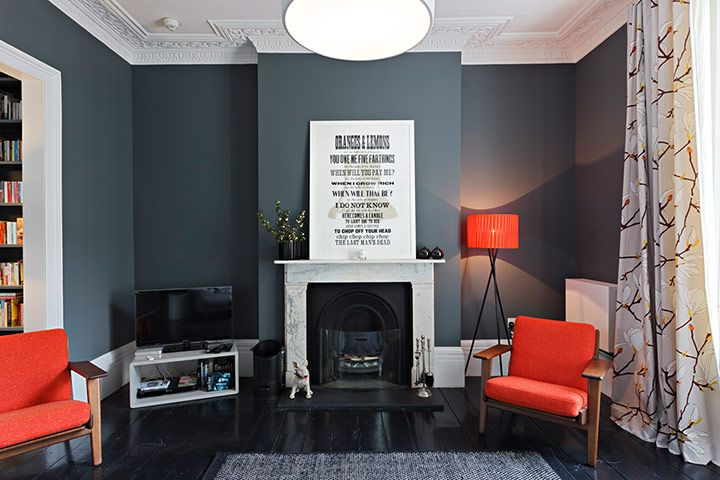 In the other reception room lead grey walls – Down Pipe by Farrow & Ball – contrast with orange GE290 chairs by Hans J Wegner and Marimekko curtains in magnolia