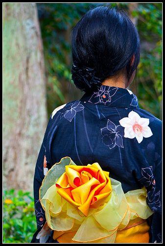 """Musubi o Lazo de obi. Se dice que existen unas quinientas formas diferentes de atarse un lazo de obi. Los musubi, tienen en Japón un significado que va más allá de la mera dificultad técnica, ya que a menudo esta palabra se escribía con los caracteres de """"espíritu viviente"""", al considerar que buenos espíritus habitaban los lazos. En el pasado, de hecho, se entregaban lazos como prenda de amor o incluso como amuleto contra los malos espíritus y hoy en día todavía se utiliza esta palabra para…"""