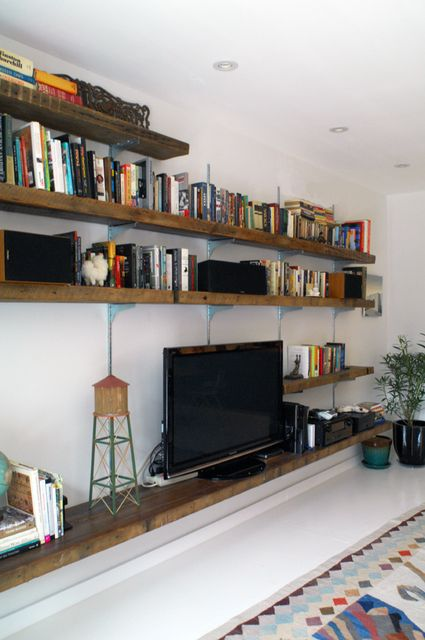 """I love the """"rustic"""" (is that the right word?) shelving and how they are storing so many books with the tv.  I like the different lengths of sshelves a lot, too."""