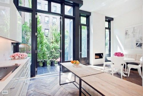 The floor to ceiling windows are intensely great. Not to mention the weathered herringbone floor and modern white kitchen. LOVE.