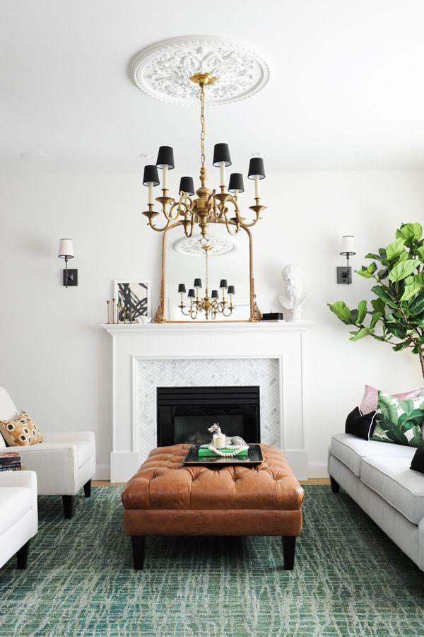 tufted ottoman, jade green rug, brass chandelier, gilt mirror, marble fireplace surround