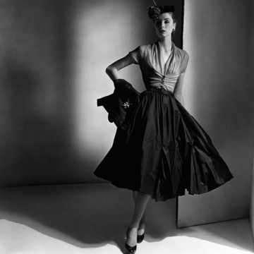 She wears a rose chiffon gathered bodice and wrap jacket with a black tulip-pleat skirt and pillbox hat, all by Dior. A Louis XIV pin completes the look. The dramatic image appeared in the March 15, 1952 Vogue issue.