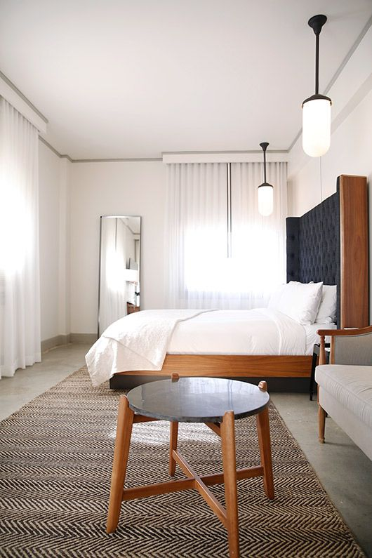 a white bedroom with strong wood details fore more hotel decor ideas http - Beaded Inset Hotel Decoration