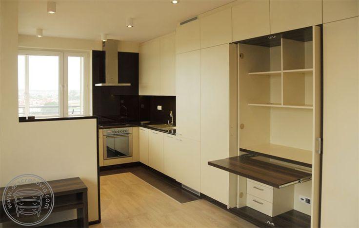Kuchnia w małym mieszkaniu, połączona z wysoką zabudową szaf, z ukrytym miejscem do pracy. Całość w jasnym pastelowym kolorze, który nie zmniejsza optycznie przestrzeni mieszkania.