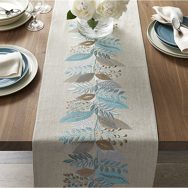 Delicate botanical design embellishes gorgeous linen runner with silky embroidery in springtime blues and neutrals.