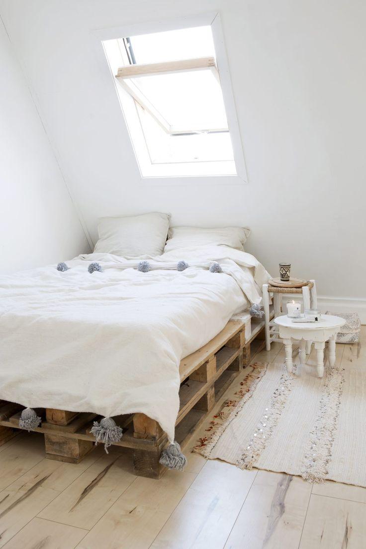 Chambre naturelle. Bois, blanc et plaid pompons
