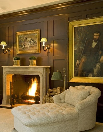 Cozy family room in Virginia - brass sconces and lamp, paintings, clipped plants, chaise longue in Bennison's Oakleaf - William Hodgins - House Beautiful