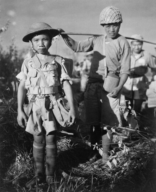 This Chinese soldier, age 10, with heavy pack, is a member of an army division boarding a plane returning them to China, following the capture of Myitkyina airfield, Burma, under the allied command of US Major General Frank Merrill, May 1944.