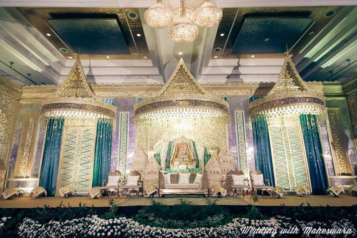 Bentuk pelaminan dan backdrop pernikahan adat Minangkabau Sumatra Barat yang terlihat didominasi warna emas dan biru. Terlihat cerah.