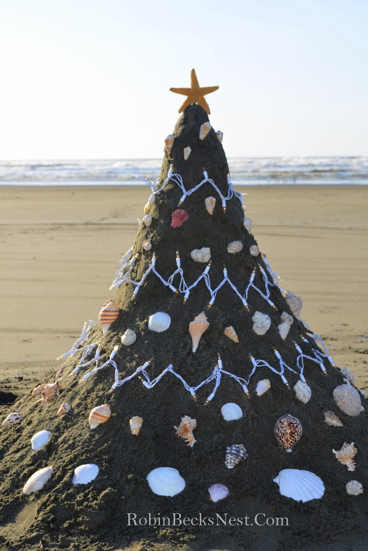 Sand Christmas tree on the beach decorated with lights and shells.