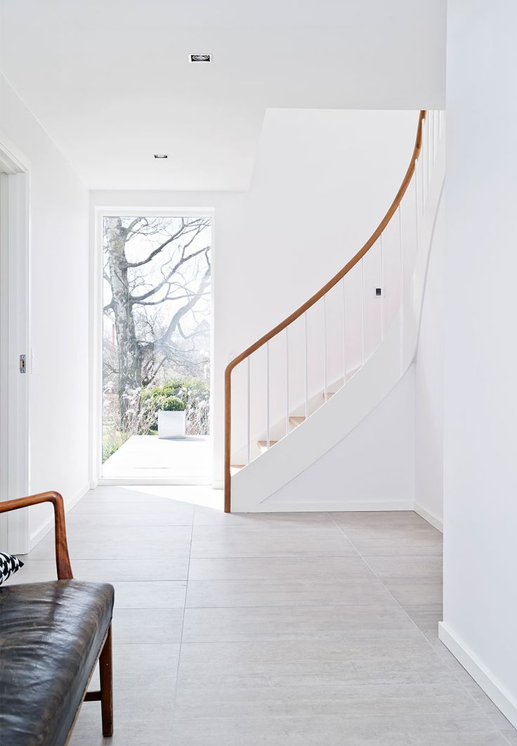 Wide staircase with steps and the round handrail in oak. A roof window by the stairs gives a fine daylight both to the stairs and hallway.