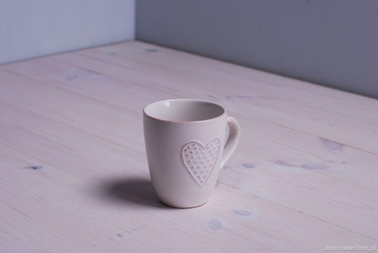 Biały kubek z motywem serca i delikatnymi przetarciami na wypukłościach. Idealny na zimowe wieczory z z ciepłą herbatą lub czekoladą.