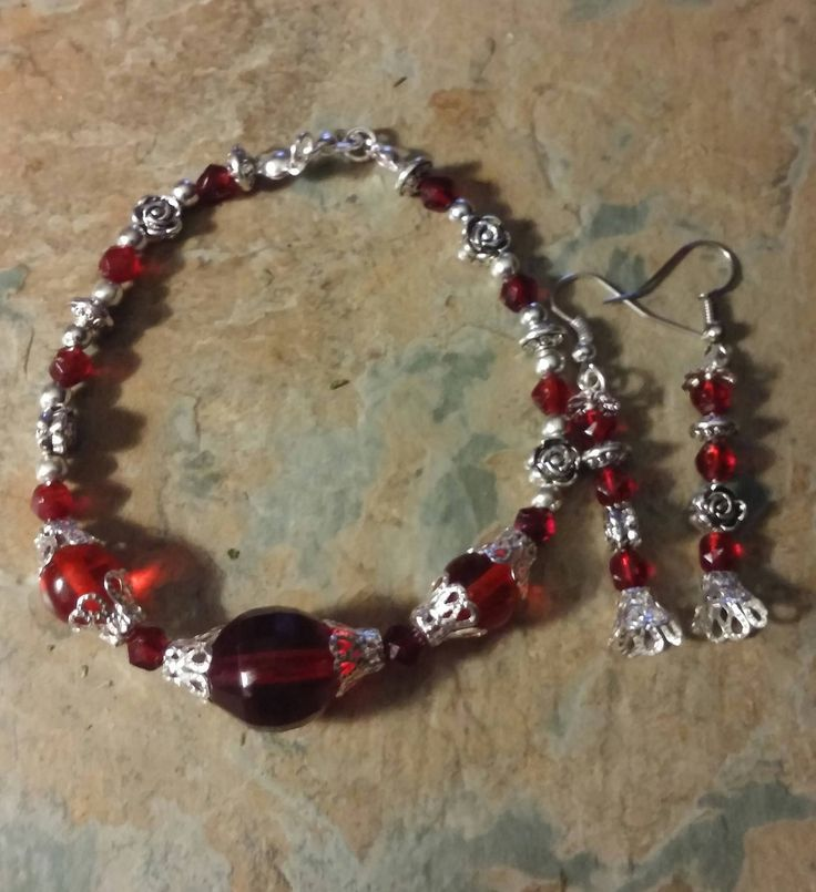 A stunning ruby red glass handmade with silver detail and roses, lobster clasp bracelet and matching earrings by SpryHandcrafted on Etsy