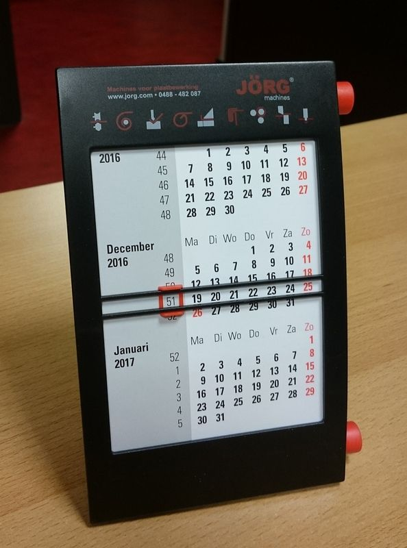 """Over de driemaands bureaukalender: """"Mooie en handige kalender op het bureau. 3 Maanden in één oogopslag. De bedrukking valt wat tegen op de zwarte ondergrond. De rode inkt is te transparant, waardoor het zwart er doorheen komt en de kleur rood te donker wordt. De had net zo helder moeten zijn als de rode knoppen. Levering was iets later dan gepland. Over het algemeen levert van Helden eerder dan gepland."""""""