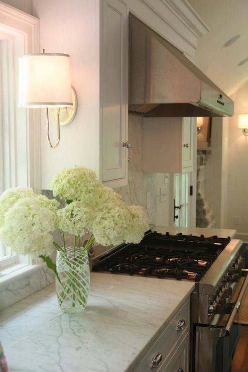 White/carrera/stainless-Sconces mounted on side of cabinet