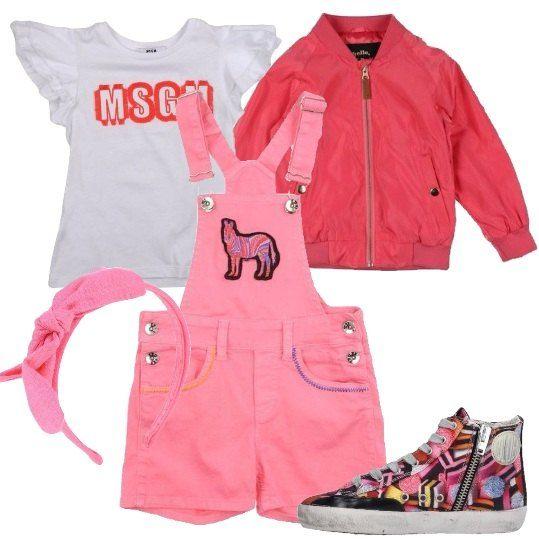 Salopette in denim rosa con pantalone corto tasche e bottoni laterali, t-shirt con logo stampato, bomber con cerniera, sneakers alte con stampa astratta multicolore, cerchietto rosa con fiocco.